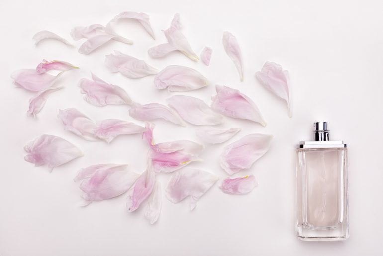 pale pink perfume bottle with flower petals coming out