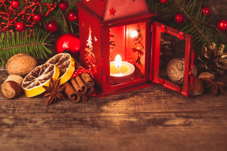a candle sat in a red lantern, surrounded holiday bits, cinnamon, berries