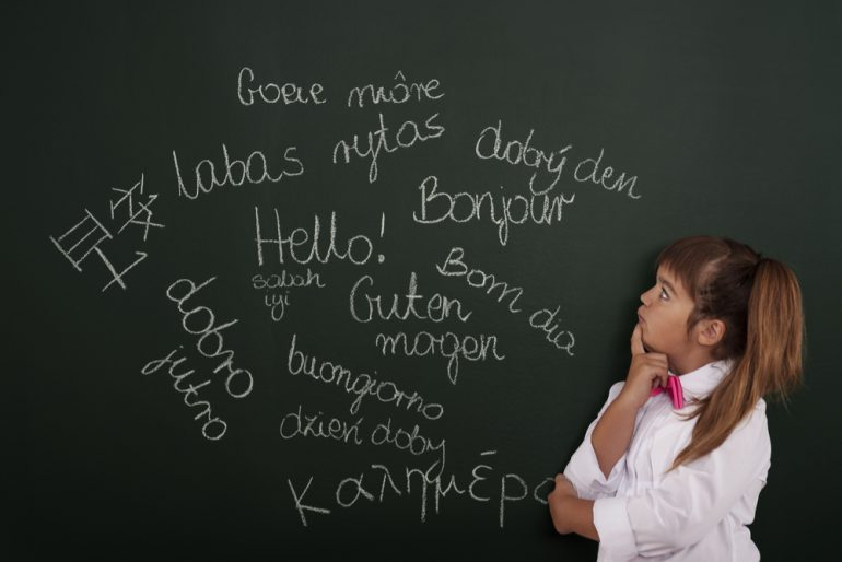 young girl looking at foreign languages on blackboard