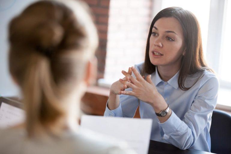 stern businesswoman sat at desk, speaking to unpictured employees