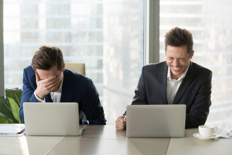two laughing men sat at computers
