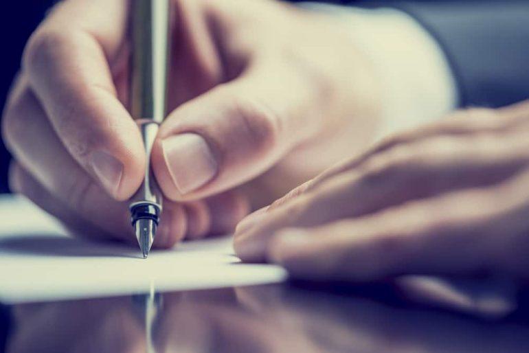 hand holding pen onto paper