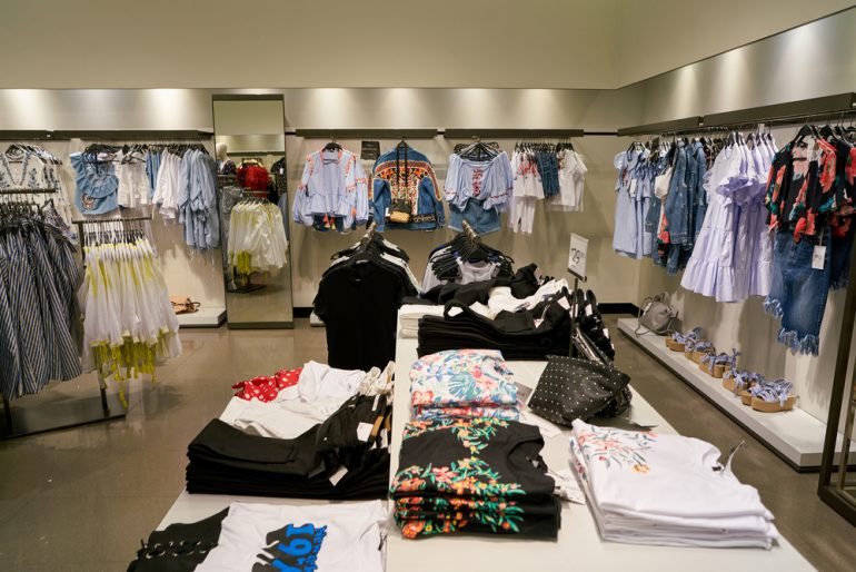 Inside of a Zara store, clothes on racks and on display