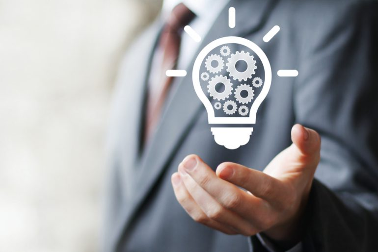 Man in suit holding an engineering light bulb icon