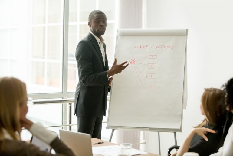 man standing in front of drawing pad in front of meeting