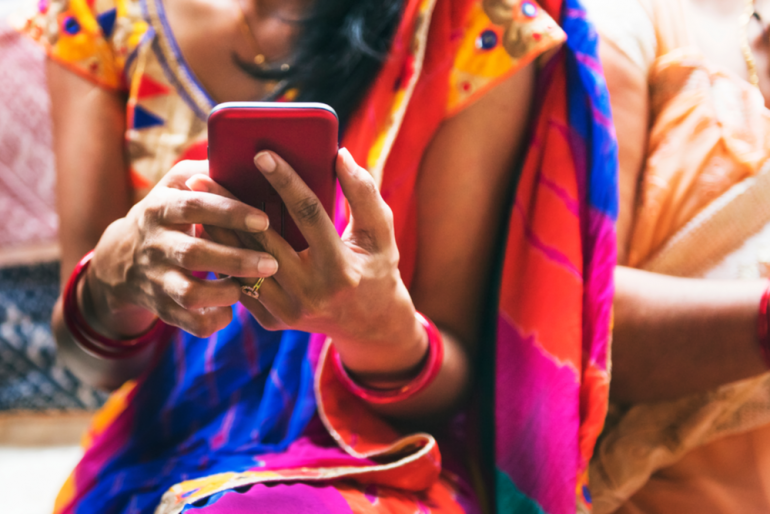 Indian woman making a mobile payment on her mobile phone