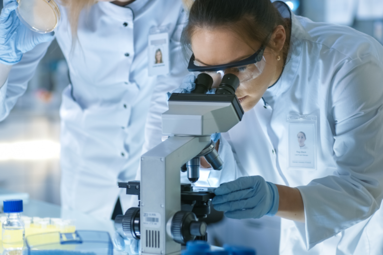 Medical Research Scientist Drops Sample on Slide and Her Colleague Examines it Under Microscope.
