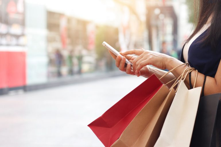 woman holding shopping bags and scrolling on mobile phone