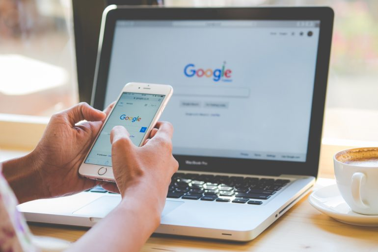 person holding a mobile phone in front of desktop, both have google search engine up