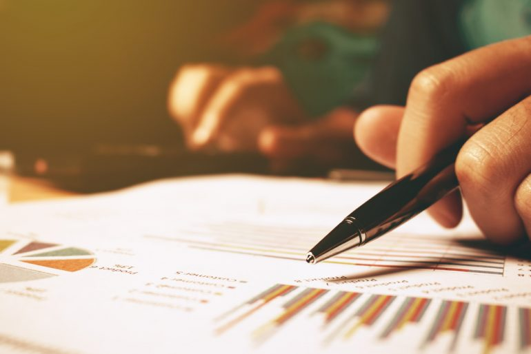 Woman holding a pen over a financial report