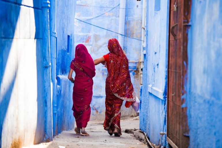 Two women dressed in the traditional Indian Saree are walking through the narrow streets - cross-border
