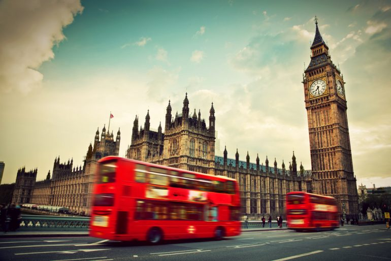 ondon, the UK. Red bus in motion and Big Ben, the Palace of Westminster. The icons of England in vintage, retro style