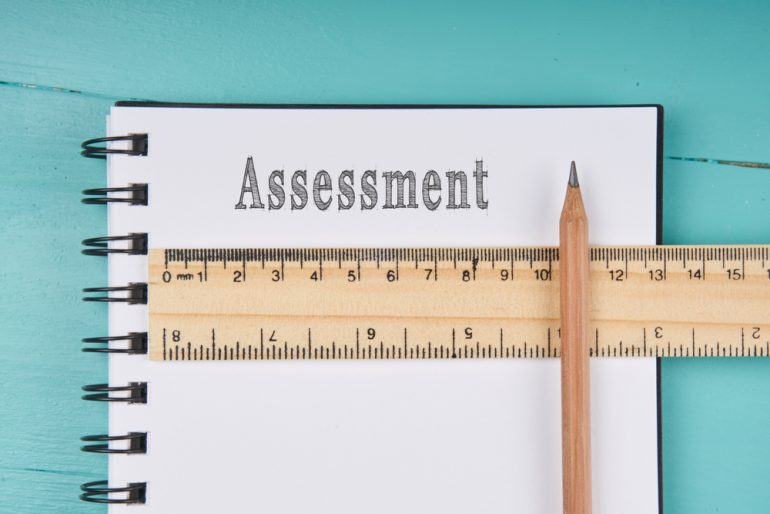 ssessment word on notebook, wooden ruler and pencil on blue wooden background. Top view. Business concept.