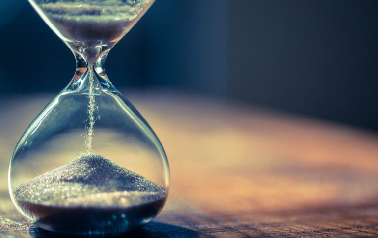 Sand running through the bulbs of an hourglass measuring the passing time in a countdown to a deadline, on a dark background with copy space.