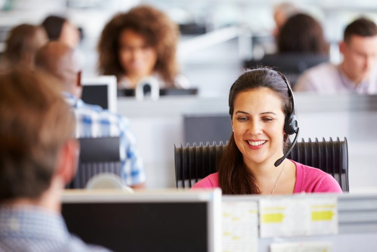 A woman in a call centre smiling while taking a call