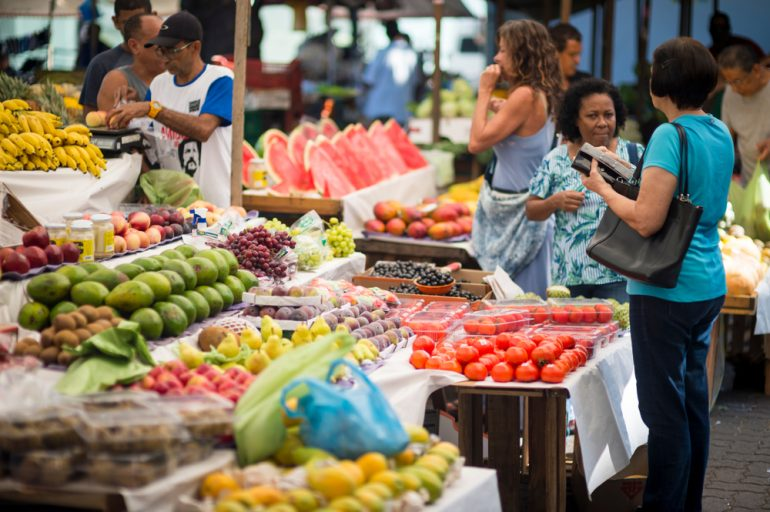 Vendors tend to customers at the weekly tropical fruit market in Ipanema.