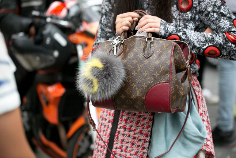 Woman holding Louis Vuitton fashion bag during Paris fashion week