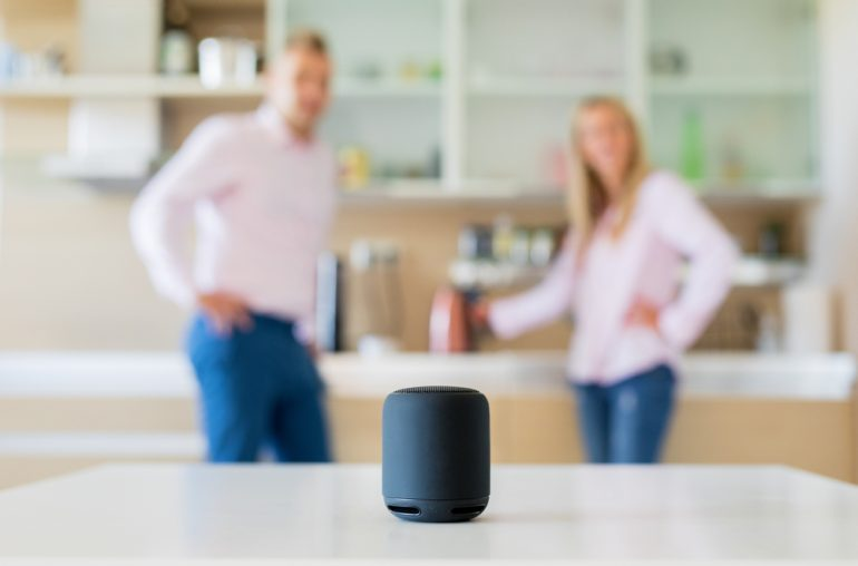 A couple standing in a kitchen using a voice assistant decive