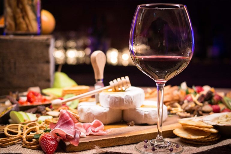 A wine and food tasting platter with wine, cheese and cured meats.