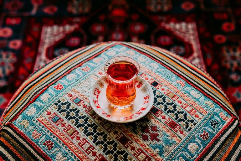 A glass of Iranian tea being served on a hand-stitched pillow