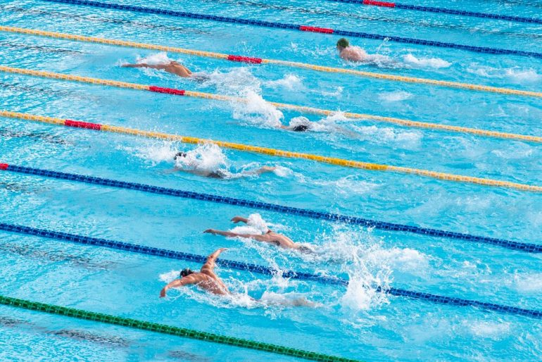 Olympic swimmers swimming in a pool to the finish line
