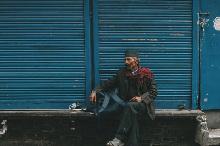 Older indian man sitting against the shutters of a closed shop