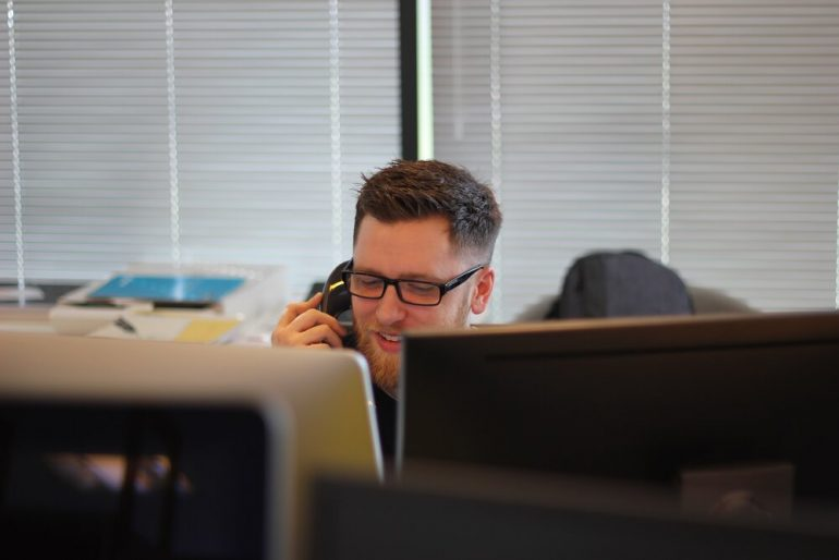 Man speaking to a customer on the phone in a call centre