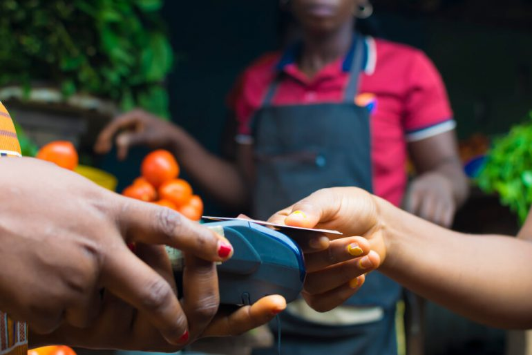 African woman paying for goods as a local vegetable stall with contactless payment