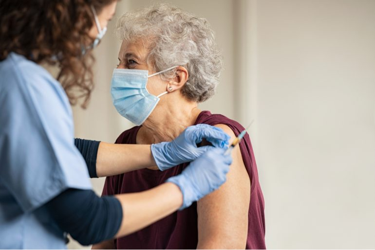 Doctor giving a senior woman a vaccination at hospital.