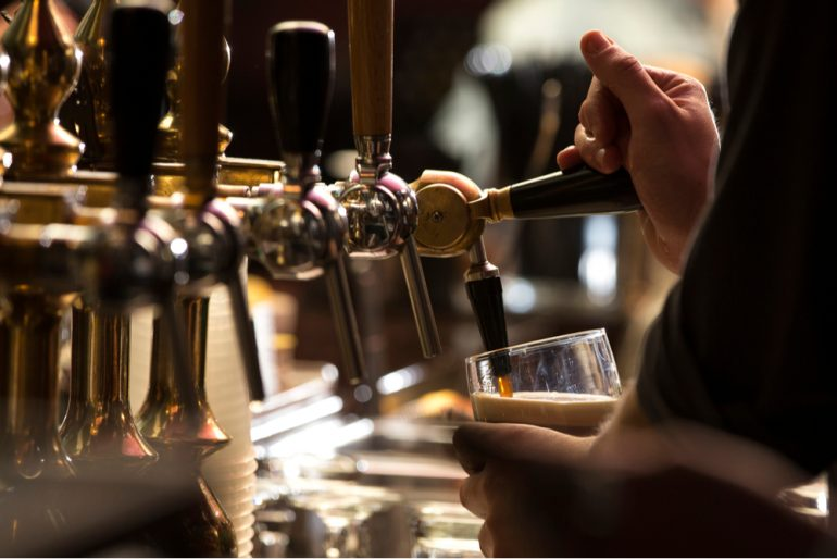 a bartender pouring a dark stout beer on tap in a bar