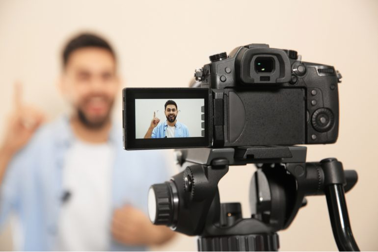 Man in front on a camera filming a video