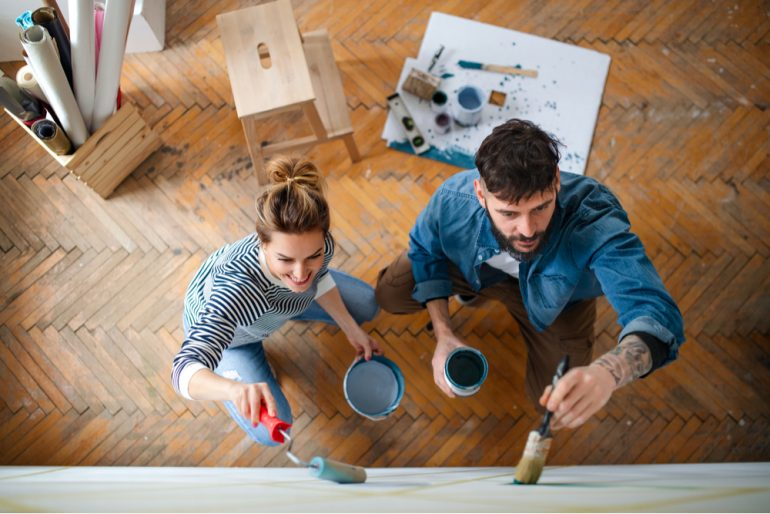 Top view of couple painting wall indoors at home
